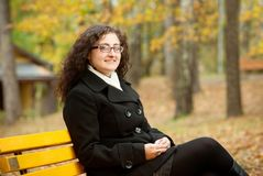 Smilling woman sitting on bench Stock Image