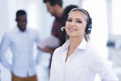 Smilling young business woman in front of her team. Stock Photo
