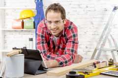 Smilling young man using the tablet for DIY Stock Image