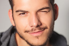Smilling young man is winking his eye Stock Image