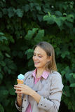 Smilling young woman with ice cream in nature Royalty Free Stock Image