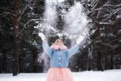 Smilling young woman thowing snow in the air at sunny winter day royalty free stock photo