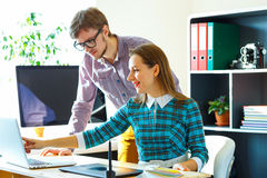 Smillingl young woman and man working from home Stock Photography