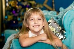 Smillings-Mädchen liegt auf einem blauen Sofa auf dem Hintergrund eines Weihnachtsbaums lizenzfreies stockfoto