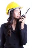 Smillings vrouwelijke bouwvakker die met een walkie-talkie spreken Stock Afbeeldingen