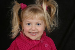 Smilng Girl. A cute preschool girl smiling in a pink sweater Royalty Free Stock Photos