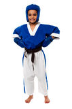 Smilng karate kid ready to fight out. Little girl dressed in sporty karate attire Stock Photography