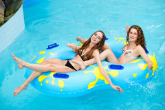 Smilng kvinnor i bikiniridning på vattenglidbanan i aquaen parkerar Royaltyfria Bilder