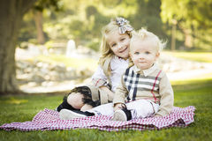 Smilng Little Girl with Her Baby Brother at the Park. Sweet Little Girl Sitting with Her Baby Brother on a Picnic Blanket Outdoors at the Park Royalty Free Stock Photography