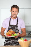 Smilng man in fixing dinner Stock Image