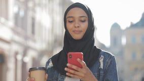 Smilng moslimvrouw die hijab headscarf het lopen in het stadscentrum, het gebruiken van smartphone en het drinken van koffie drag stock video