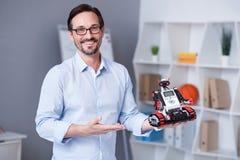 Smily και ελκυστικός παρουσιαστής που καταδεικνύουν λίγο ρομπότ Στοκ Εικόνα