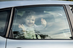 Smily baby girl looking out a car window Stock Photos
