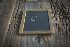 Simple Smiley on a old Chalkboard. Nice smiley drawing on an old chalkboard . Table made out of old barn wood Stock Image