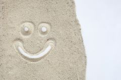 Smily face drawn on sand in white isolated background.  stock photography