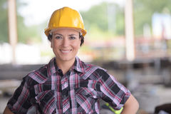 Smily female worker wearing yellow helmet. Smily female worker wearing a yellow helmet Stock Photo