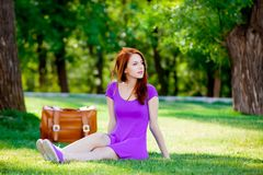 Smily redhead girl with suitcase. At summertime park outdoor Stock Photo