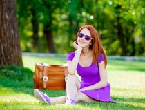 Smily redhead girl in sunglasses with suitcase. At summertime park outdoor Royalty Free Stock Photos