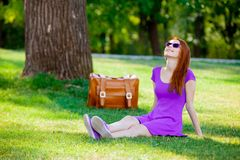 Smily redhead girl in sunglasses with suitcase. At summertime park outdoor Royalty Free Stock Photo