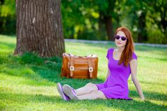 Smily redhead girl in sunglasses with suitcase. At summertime park outdoor Stock Photo