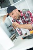 Smily repairman fixing computer unit. Man Royalty Free Stock Image