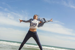 Smily teenager jumping in the seashore of the beach in a clear d Stock Photo