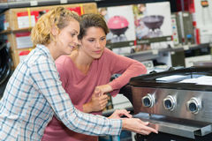 Smily woman buying oven in hypermarket Stock Image