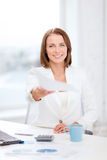 Sming businesswoman giving papers in office Royalty Free Stock Photos