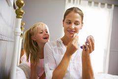 Smink för arbetande mamma för dotter hållande ögonen på pålagt royaltyfria foton