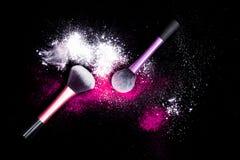 Sminkborsten med spillt vitt pulver blänker damm på svart bakgrund Makeupborste på partiet för ` s för nytt år med ljusa färger Royaltyfria Foton