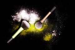 Sminkborsten med spillt vitt pulver blänker damm på svart bakgrund Makeupborste på partiet för ` s för nytt år med ljusa färger Arkivfoto