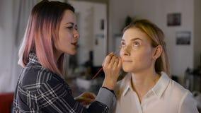 Sminkkonstnär i studion som gör makeupskönhetflickan stock video