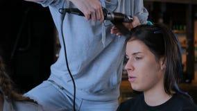 Sminkkonstnär och frisör som arbetar med kvinnaklienten arkivfilmer