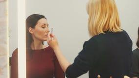 Sminkkonstnär på arbete med modellen i spegelreflexionen lager videofilmer