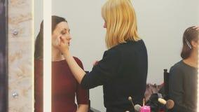 Sminkkonstnär på arbete med modellen i spegelreflexionen Royaltyfri Foto