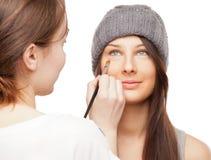 Sminkkonstnär som applicerar makeup på aktörs framsida royaltyfri fotografi