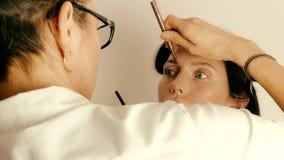 Sminkkonstnär som applicerar smink på framsida för modell` s arkivfilmer