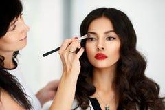 Sminkkonstnär som applicerar yrkesmässigt smink på fa för ` s för ung kvinna Arkivfoton