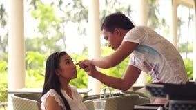 Sminkkonstnär som gör ögat som fodrar till en ung kvinna stock video