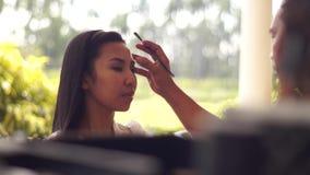 Sminkkonstnär som gör ögat - krön till en ung kvinna stock video
