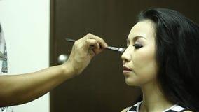 Sminkkonstnär som gör ögonskuggor till en ung kvinna lager videofilmer