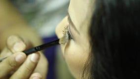 Sminkkonstnär som gör ögonskuggor till en ung kvinna stock video