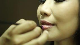 Sminkkonstnär som gör läppstift till en ung kvinna arkivfilmer