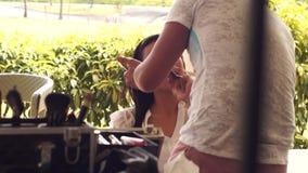 Sminkkonstnär som gör på rodnad till en ung kvinna lager videofilmer