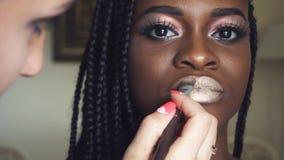 Sminkkonstnär som gör sminket för ung härlig afrikansk amerikanmodell med flätade trådar closen tappar extremt falla över red upp stock video