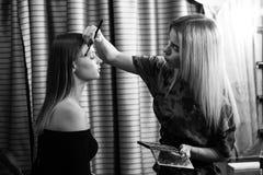 Sminkkonstnär som gör yrkesmässigt smink av den unga kvinnan Arkivbilder