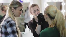 Sminkkonstnär, student och modell Lärande processen Ung blondin Ögonbrynen för teckning för sminkkonstnär till ett nätt lager videofilmer