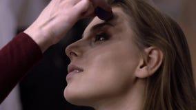 Sminkkonstnären applicerar rodnad på modellnärbilden arkivfilmer