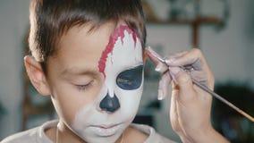 Sminkkonstnären gör det pojkehalloween sminket Konst för allhelgonaaftonbarnframsida lager videofilmer
