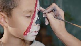 Sminkkonstnären gör det pojkehalloween sminket Konst för allhelgonaaftonbarnframsida arkivfilmer
